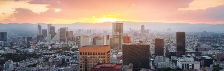 Aerial view from Torre Latinoamericana of Mexico city downtown skyscrappers and mountains at sunset