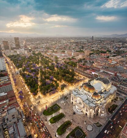 Mexico city aerial view from Torre Latinoamericana. Palacio de Bellas Artes, Alameda Central and downtown in lights at sunset.