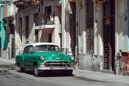 Vintage green car parked on the street of Havana, Cuba