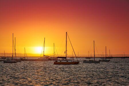 Vivid sunset at marina, silhouettes of yachts against orange sky, La Paz, Mexico
