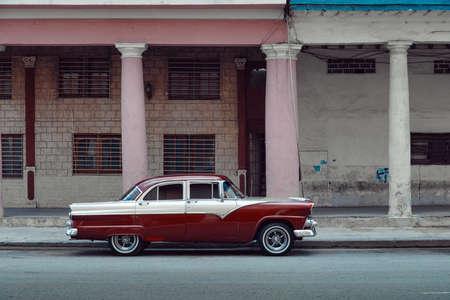 Shiny red retro car parked on the street of Havana, Cuba