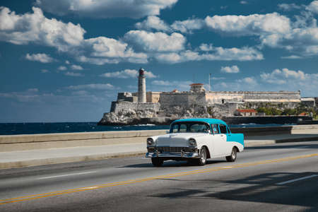 Retro car on the embankment of Havana, Cuba. El morro castle and lighthouse on background, shot with panning.