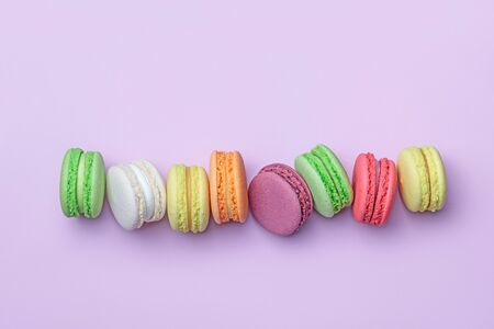 Top view of colorful macaron biscuits in a row on pastel color block background, flat lay Imagens