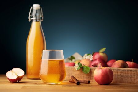 Glass of homemade apple cider or juice, red fresh apples from the garden and a bottle on background  Imagens