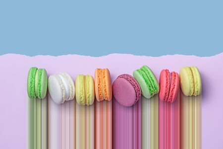 Top view of colorful macaron biscuits in a row on pastel color block background with torn paper edge, flat lay, pixel stretch
