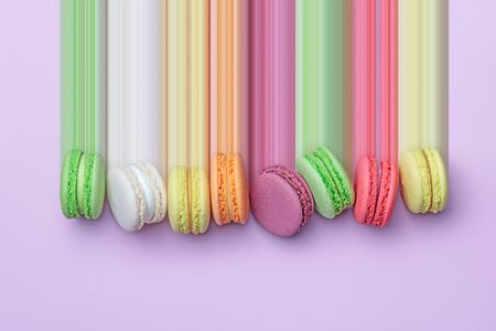 Top view of colorful macaron biscuits in a row on pastel color block background, flat lay, pixel stretch