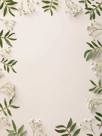 Frame of white flowers and green leaves on biege white background