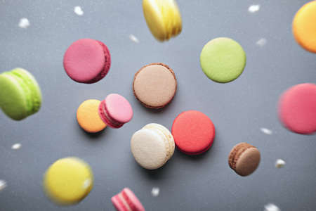 Colorful assroted macarons in motion falling with powdered sugar on grey background