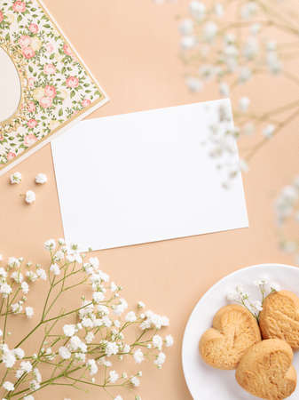 Romantic stationery flat lay with blank greeting card and white flowers on beige background Imagens