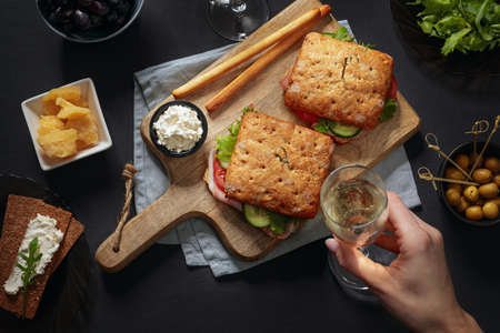 Flat lay with sandwiches with parma served on cutting board and appetizers around