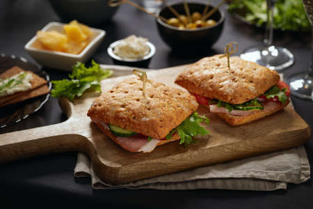 Sandwiches with parma served on cutting board and appetizers around