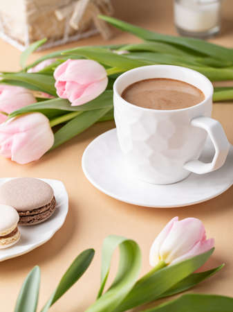 Romantic still life with a cup of cocoa, macarons and tulips