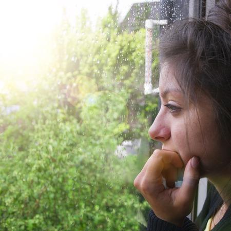Smutna dziewczyna wygląda przez okno, pada deszcz. Kobieta z ładny wyglądający słyszeć