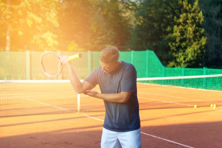 Handsome man on tennis court. Young tennis player. Pain in the elbow with sunlight in background