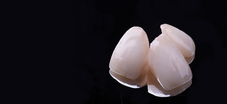 dental ceramic veneers and crowns isolated with mirror background.