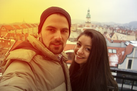 Loving couple taking selfie in winter with city panorama.