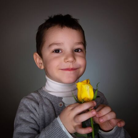 Romantic Boy with smile and flowers on black studio background