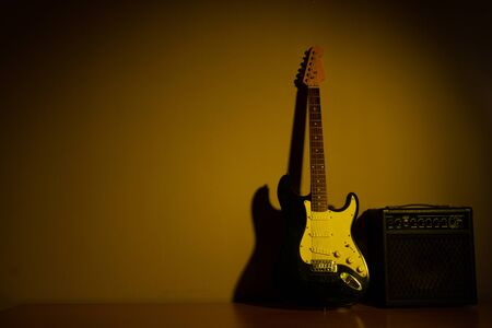Yellow light electric guitar in front of a vintage wall Imagens