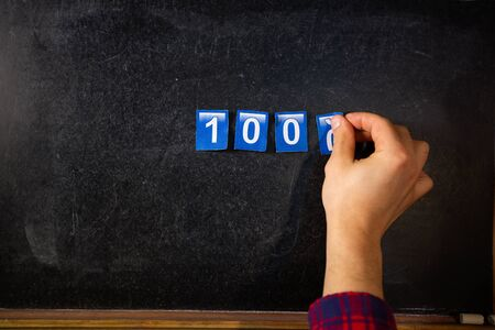 Hand writes the number of subscribers on the board