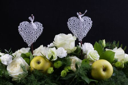 two hearts with green apple and flowers. Black background Imagens