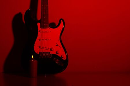 electric guitar in front of a vintage wall with shadow