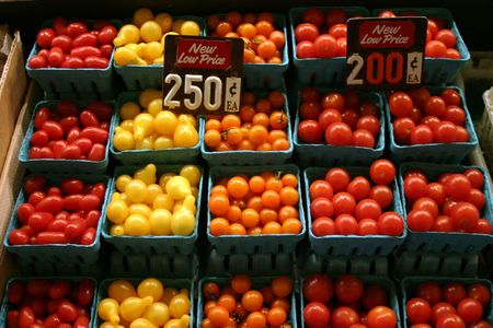 pike place: red,yellow,and orange tomatoes for sale at a farmers market