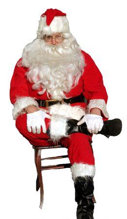Santa Claus sits cross legged on a chair Imagens