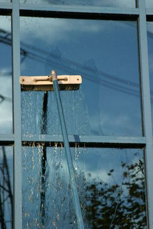 window washer: Window Washer washing a window with spot free water and an extention pole Stock Photo