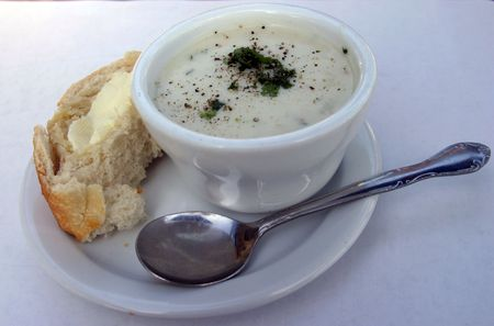 chowder: clam chowder in a bowl with french bread and butter