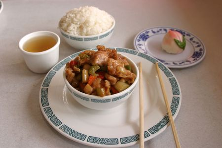 bean curd: kung pow chicken with steamed rice green tea chops sticks and a bean curd desert in a chinese restaurant