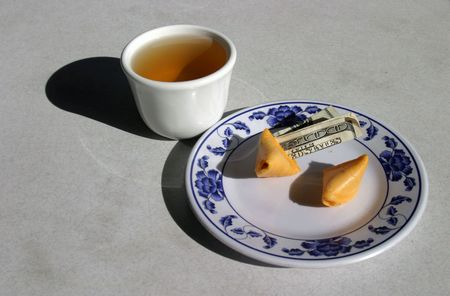 resturant: fortune cookie with a $100.00 dollar bill comming out and green tea in a chinese resturant Stock Photo