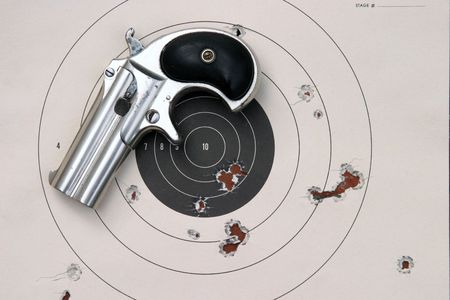 Circa 1889, Model 95, Type II Model 3 Double Derringer on a paper target with bullet holes in it
