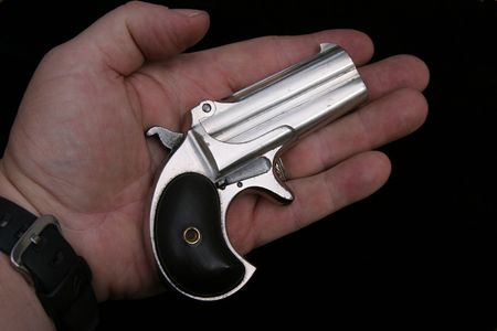 Circa 1889, Model 95, Type II Model 3 Double Derringer in the palm of a mans hand showing its true small size