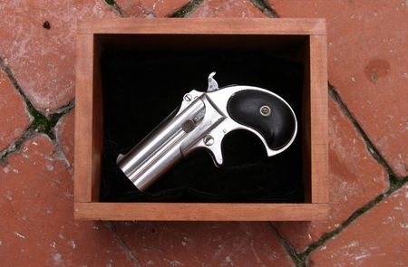 Circa 1889, Model 95, Type II Model 3 Double Derringer in its wooden box on black felt on red brick outside