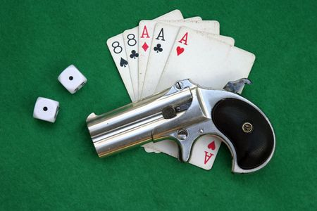 Circa 1889, Model 95, Type II Model 3 Double Derringer on green felt card table with aces and eights (aka a Dead Mans Hand) and snake eye dice Stock Photo - 295694