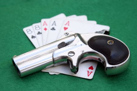 Circa 1889, Model 95, Type II Model 3 Double Derringer on green felt card table with aces and eights (aka a Dead Mans Hand)