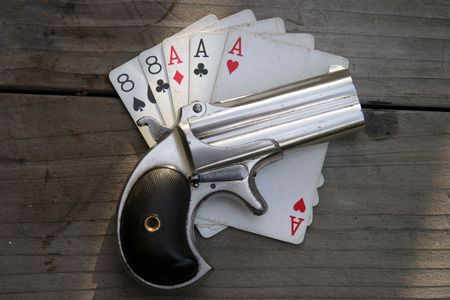 Circa 1889, Model 95, Type II Model 3 Double Derringer on antique wooden table with aces and eights (aka a Dead Mans Hand) Stock Photo - 295708
