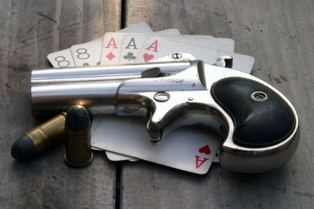 hideout: Circa 1889, Model 95, Type II Model 3 Double Derringer on antique wooden table with aces and eights (aka a Dead Mans Hand) and ammo Stock Photo