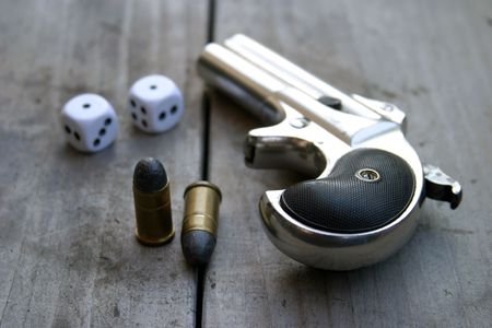 Circa 1889, Model 95, Type II Model 3 Double Derringer on antique wooden table with dice and ammo Banco de Imagens