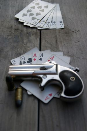 eights: Circa 1889, Model 95, Type II Model 3 Double Derringer on antique wooden table with aces and eights (aka a Dead Mans Hand) and ammo Stock Photo