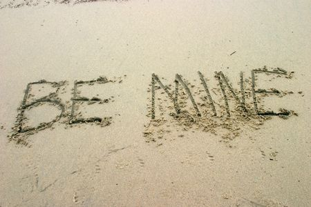 Be Mine written in the sand on the beach