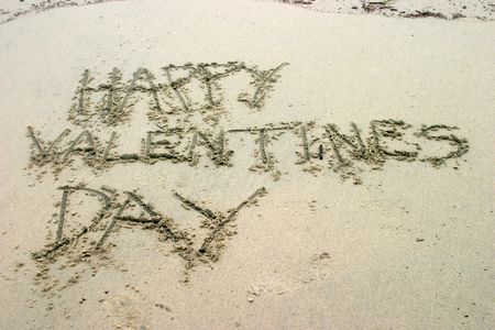 Happy Valentines Day written in sand on the beach photo