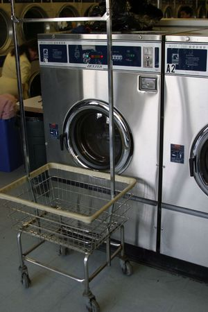 industrial dryers in a laundry mat with an empty laundry basket