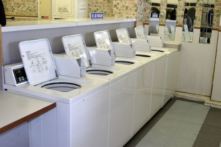 coin operated washing machines lined up and ready to wash in a Laundry mat