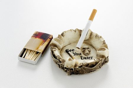 Cigarette in skull ashtray, with See You Later motif and matches on a tabletop photo