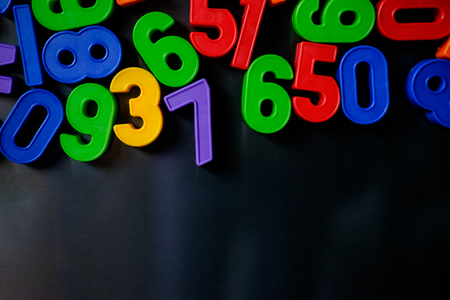 Colorful magnetic numbers and letters grouped on the fridge Stock Photo