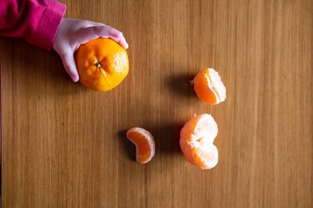 Baby s hand manipulating different fruits on a wooden table