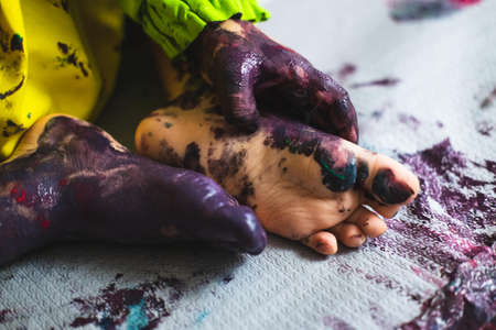 Little kid hands and feet covered with multiple colours