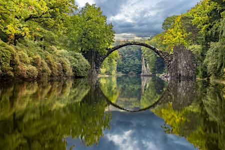 Autunno nel parco Kromlau, Ponte del Diavolo Archivio Fotografico - 67303546
