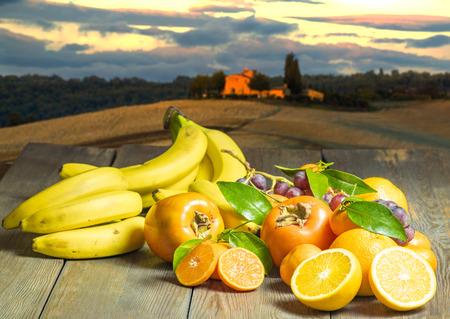 Las frutas con el famoso paisaje de la Toscana en el fondo de la salida del sol